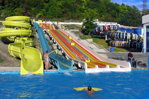 Крученые и прямые разноцветные горки в чистом голубом бассейне