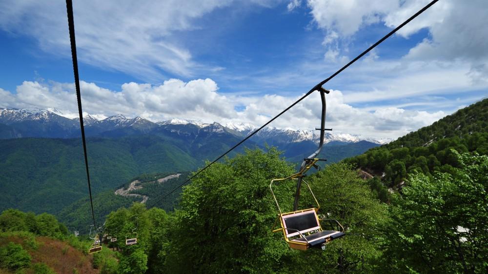 Канатная дорога в летнее время пролегающая над зелеными горами