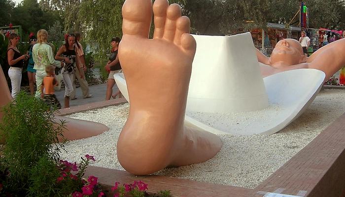 Памятник загорающему мужчине в песке
