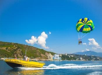 Парашютист над синим морем у желтого катера