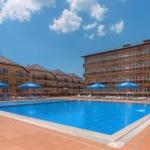 Фасад отеля Ателика Гранд Прибой с большим бассейном и голубыми шезлонгами