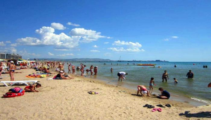 Пологий песочный пляж полный отдыхающих туристов при отеле
