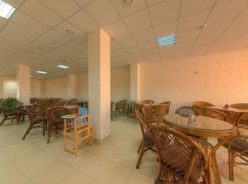 Уютное помещение кафе с плетеными стульями и круглыми столиками