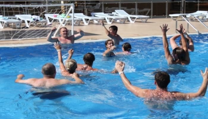 Отдыхающие в голубой воде бассейна во время веселой игры в поло