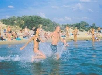 Весело бегущие по пологому пляжу люди
