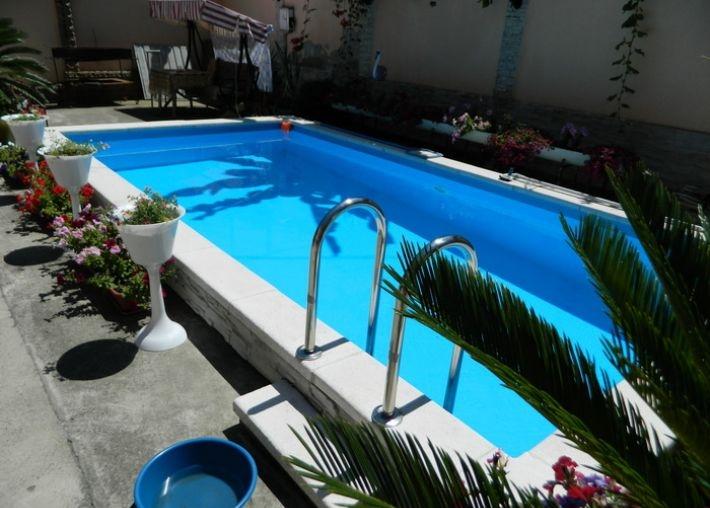 Изящный украшенный зеленью бассейн с чистейшей водой и всеми удобствами