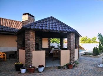 Передняя сторона дома с треугольной крышей и каменными колоннами