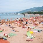 Наполненный отдыхающими туристами и жителями города Центральный пляж в Геленджике