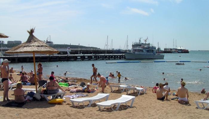 Белые лежаки на очищенном пляже и корабли на дальнем плане