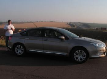 Обыкновенный серый автомобиль на дороге под заходящим солнцем