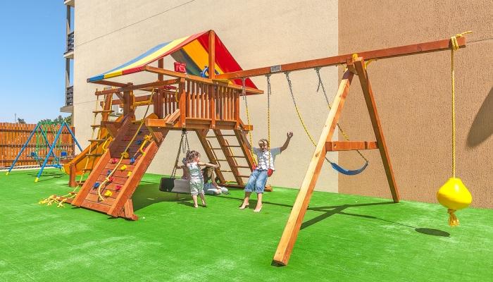Освещенная солнцем детская площадка с радостными маленькими постояльцами