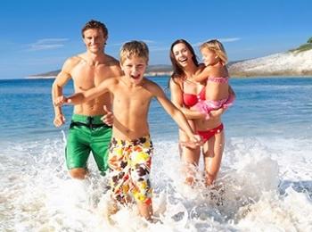 Веселый отдых всей семьей на пляжном побережье в брызгах воды