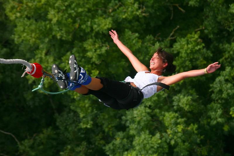 Прыгающая на резинке с высоты девушка на фоне летней зелени