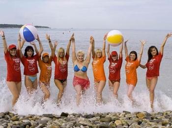 Яркая группа аниматоров с разноцветными мячами на каменистом пляже