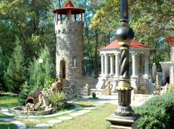 Небольшой каменный замок с обозревательной башней в старом парке