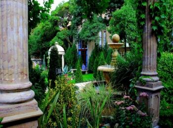 Сплошь покрытый зеленью старый парк с колоннами и фонтаном