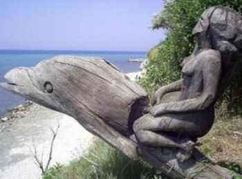 Деревянный старый памятник с оседланным девушкой дельфином