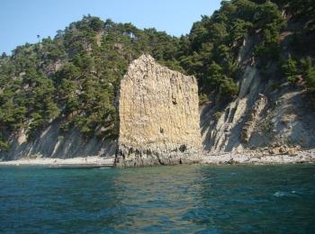 Одинокая скала Парус посреди Черного моря у зеленых скалистых берегов