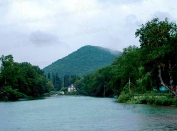 Голубая река и пышные зеленые берега с высокой горой вдалеке