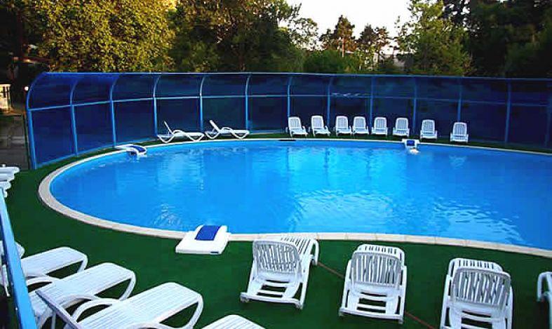 Изящный ярко-голубой бассейн необычной формы с удобными лежаками