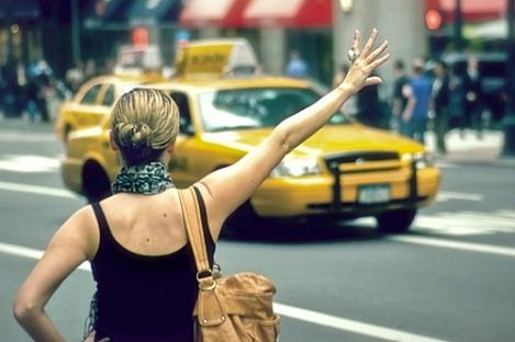 Девушка со светлыми волосами ловит такси на широкой дороге