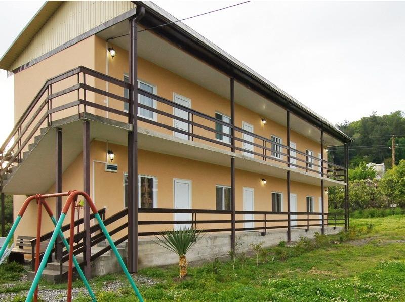 Двухэтажный гостевой дом с перилами и зеленым двором