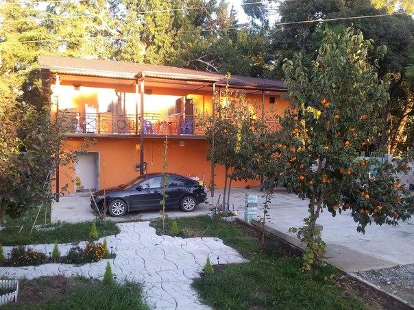 Оранжевое двухэтажное здание с черным автомобилем перед ним
