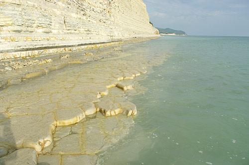Пляж с естественными каменными плитами в прозрачной воде