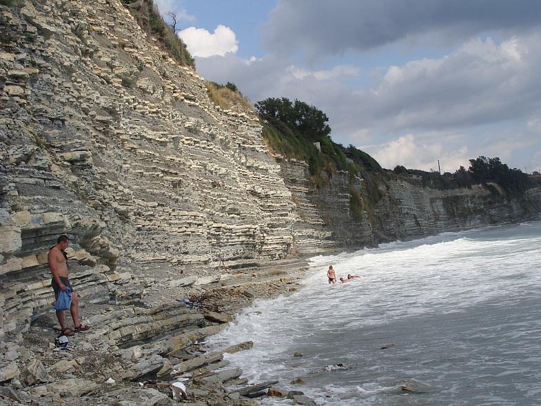 Каменистый живописный пляж у подножия скалы
