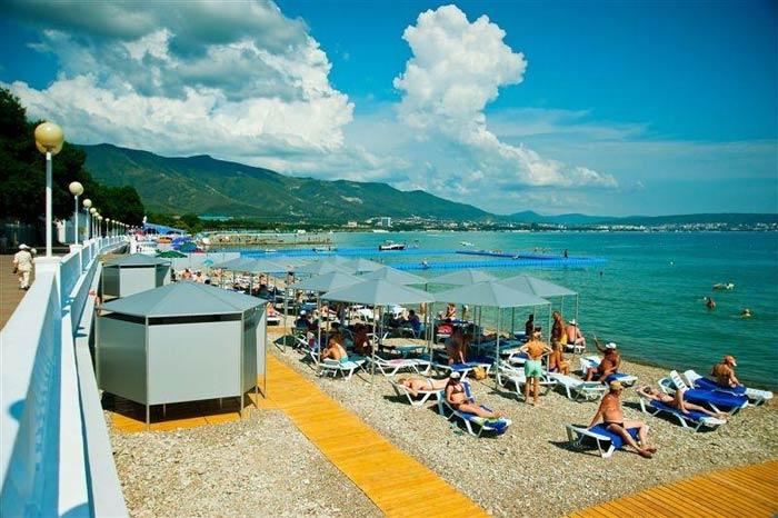 Узкий пляж с шезлонгами, лежаками и желтыми деревянными дорожка