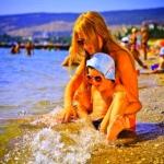 Девушка с ребенком на солнечном берегу пляжа в санатории Анапы