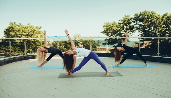 Три девушки на открытой площадке во время занятия лечебной физкультурой