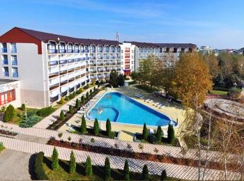 Длинное здание с красной черепицей и благоустроенным двором с ярким бассейном