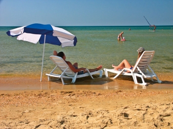 Отдыхающая под сине-белым зонтом пара женщин на аккуратном пляже