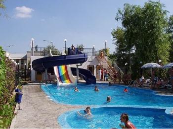 Хороший открытый бассейн с радужной горкой и купающимися детьми