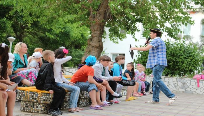 Развлекающий группу детей веселый аниматор в парке