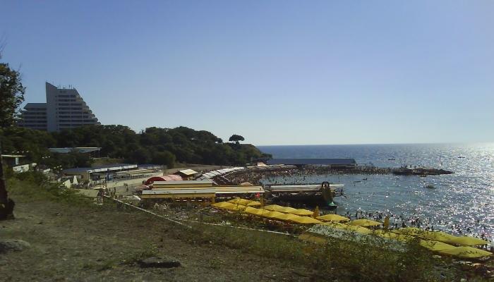 Пляжная зона санатория с желтыми навесами и многочисленными удобствами