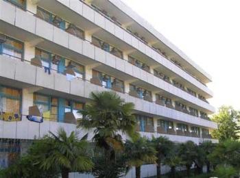 Длинное здание санатория и роскошные пальмы перед ним