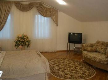 Удобный небольшой номер в бежевых тонах с двуспальной кроватью и телевизором