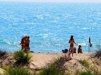 Отдыхающие идут на пляж к ярко голубому морю
