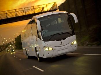 Белый автобус едет по дороге под оранжевым светом заходящего солнца