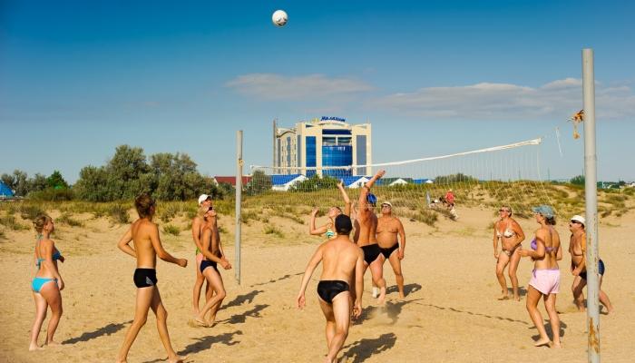 Группа туристов развлекается игрой в пляжный волейбол