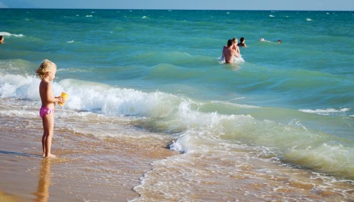 Маленькая девочка у безопасного для нее пологого побережья