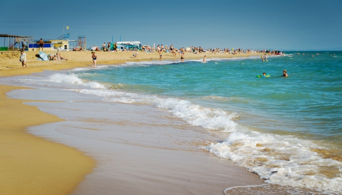 Чистый песчаный пляж с множеством посетителей у нежно-бирюзовой воды