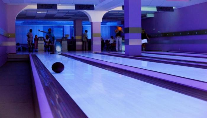 Зал с боулинговыми дорожками, освещенный фиолетовым светом