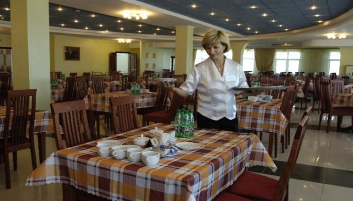 Работница пансионата обслуживает стол в столовой перед приходом постояльцев