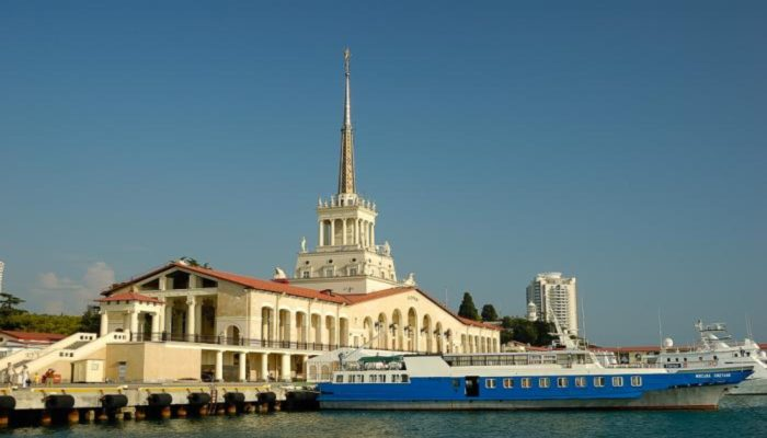 Вид на вокзал и длинное сине-белое судно для морских прогулок