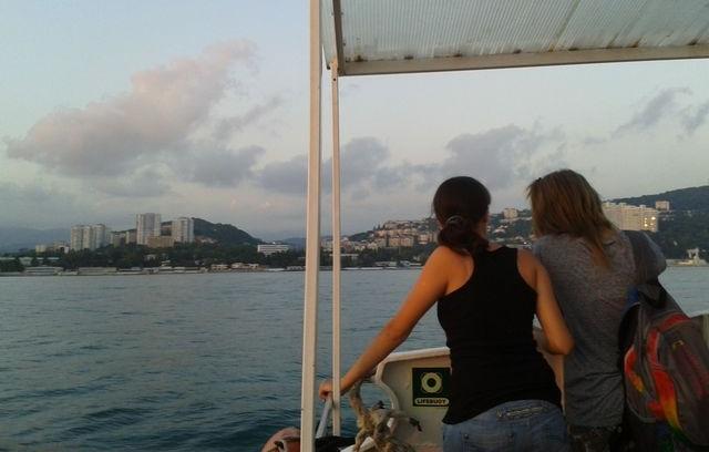 Две девушки на морской прогулке смотрят на отдаляющийся Сочи