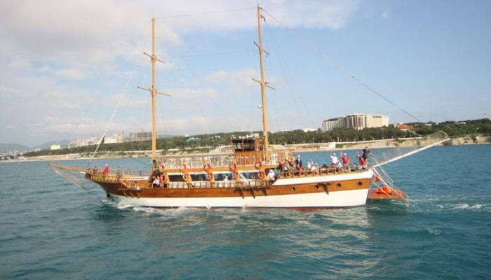 Отличное судно с деревянными мачтами вблизи от города