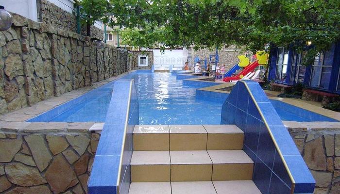 Каменный бассейн у забора с синей плиткой